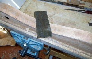 Scraping the sides of a cherry dulcimer
