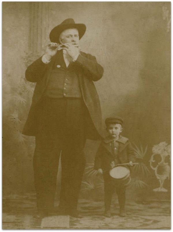 Big man playing fife, small boy playing drum