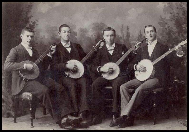 Four men playing 5-string banjos and banjo-guitars  a long time ago
