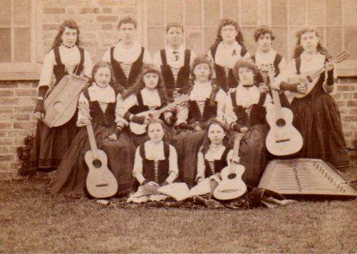 Young ladies playing zither, guitars, mandolins, and hammered dulcimer